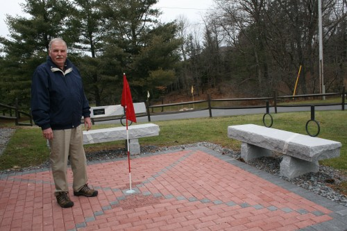"Dave Barker, Chairman of the Memorial Paver project at  Thendara Golf Club, stands on the ""putting green"" with pavers to honor those who have passed on. Photo by Carol Hansen"