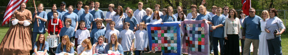 Eighth grade students and faculty pose for a photo holding quilts similar to those made during the Civil War Era and the flags of the north and the south. Photo by Carol Hansen.