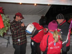 Mitch Lee holds the bucket of raffle tickets as Alex Sutherland draws the kayak winner during Inlet's Frozen Fire & Lights Celebration. Alex's father, Eric Sutherland is at far right.