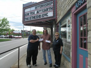 Jamie Loson, President of the Old Forge Fire Department, and Captain of the Old Forge Ambulance Core, Terry Lehnan present Bob Card of the Strand Theatre with two checks totaling $2,000. Photo by Dana Armington