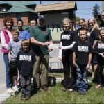 Chris Holt, left, Barb Uzdavinis, rear, and Thomas Levi, Mike Griffin representing KYAC, Cousins that Care founder Melanie Levi presenting the check, Cory Hansen, Brittney Levi, Laura Levi, Shelby Townsend, and Shawn Hansen. Photo by Michele deCamp
