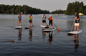 Mountainman staff demonstrate Stand Up Paddling on the Old Forge Pond. Photo by Carolynn Dufft