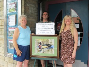 Sue Kiesel, left, recently donated this Wood Duck photograph to Bob Card, center, and Helen Zyma, right, to be raffled off on Wednesday, July 31 for a $5 donation. Photo by Dana Armington
