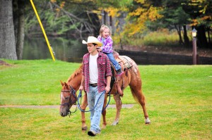 Breanna Marleau gets a ride on Walter the horse with handler Casey. Photo by Dave Scranton