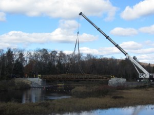 A crane positions the new TOBIE bridge from shore to shore across the Moose River. Photo by Gina Greco