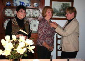 Dona Finkle, center, receives her Beta Sigma Phi pledge pin from Judy Herron. Also participating in the ceremony was Izzie Worthen, left. Photo by Karen Beck