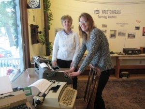 "Goodsell Museum's Kate Lewis, left,  and Kristy Rubyor try out some vintage typewriters, part of the ""Wired to Wireless"" exhibit. Photo by Gina Greco"