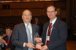 Webb Supervisor Ted Riehle, right, receives the NYMIR award from Gerry Geist, Executive Director of the New York State Association of Towns.
