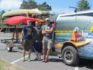 Paddlefest Prep...Matt Phaneuf, Mike Giovinco, and John Nemjo, owner of Mountainman Outdoor Suppy Company, ready a trailer of kayaks at the event's lakefront venue. Photo by Gina Greco