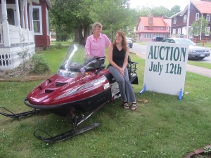 TOW Historical Director Kate Lewis and assistant, Kristy Rubyor, with an auction item, a 2001 Polaris 550 snowmobile.  Photo by Gina Greco