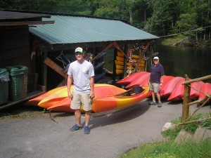 West Tickner, left, and Dick Olson readying a kayak for launch at Tickner's on the Moose River. Photo by Marianne Christy