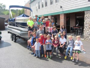 The children and staff of the Town of Webb Summer Youth Program—many of them graduates of the Kinderwood Preschool Program—pose around the 18' Bennington pontoon boat that will be raffled in support of the program. Photo by Gina Greco