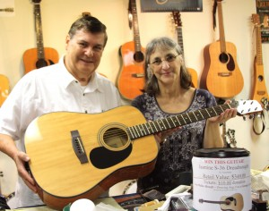 Albert Worthen and Lucy Walker with the guitar raffle prize