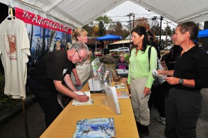 Gary and Carol VanRiper sign books and talk to visitors at the Adirondack Kids table at last year's Adirondack Kids Day in Inlet. Photo by Dave Scranton
