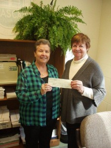 Hazel Dellavia, right, presents a donation to Lyn V. Kinney, HASCA business manager.