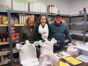 Sydney Payne, center, with Sharon and Bob Daviau at St. Bartholomew's Food Pantry. Photo by Gina Greco