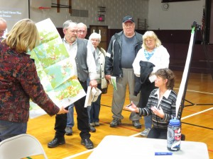 Kathy Regan, the Adirondack Park Agency's Deputy Director of Planning (kneeling at right) discusses Adirondack policy with local residents the Town of Webb school gym in Old Forge. Photo by Gina Greco