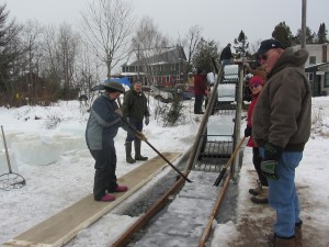 Tom Smedley, right, monitors the harvesting of ice blocks from Raquette Lake in this 2014 file photo by Gina Greco.