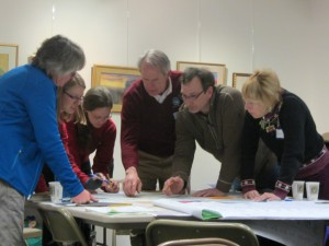 Workshop participants examined Adirondack maps at the Old Forge Library on February 25. At right are Ted Christodar, owner of Pedals & Petals bike shop in Inlet, and Carolyn Trimback of Old Forge. Photo by Gina Greco