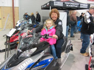 Natasha, front, and Marie LaPorte check out a new 2016 model Yamaha snowmobile at Old Forge's Snofest. Photo by Gina Greco