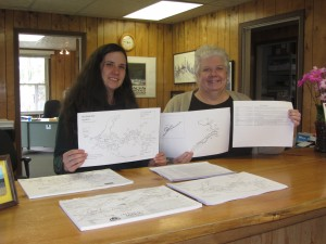 Alexis Russell and Martha Denio hold up the garage sale maps for the area's upcoming holiday weekend. Photo by Gina Greco
