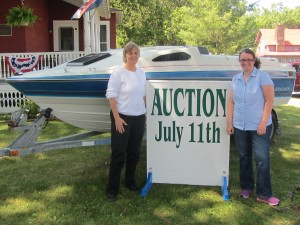 Goodsell Museum Director Kate Lewis and intern Claire Hayes with auction item, a 1988 Bayliner I/O with trailer. Photo by Gina Greco
