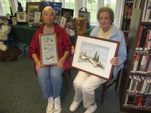 Annette Eyre, left, displays her needwork piece and Louise Watson, her painting of Bald Mountain Fire Tower. Gina Greco photo