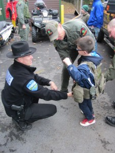 Town of Webb police  officer Kevin Birtle and DEC officer Murphy  help Seamus Birtle try  on a bullet proof vest
